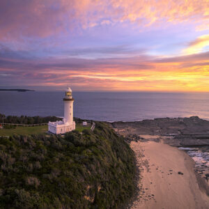 Sunrise over a lighthouse by the ocean